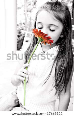 Little Girl smelling her red gerber daisy with a dreamy look on her face. - stock photo