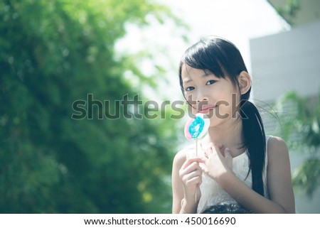 Little girl smile with sweet candy from low angle vintage style,dark tone - stock photo
