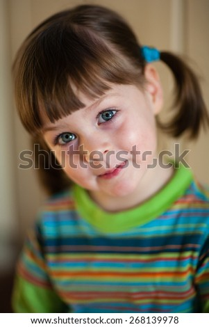 Little girl smiling - adorable young girl with ponytails looking at camera. Shallow depth of field - stock photo