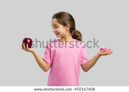 Little girl smiling and choosing between a apple and a donut - stock photo