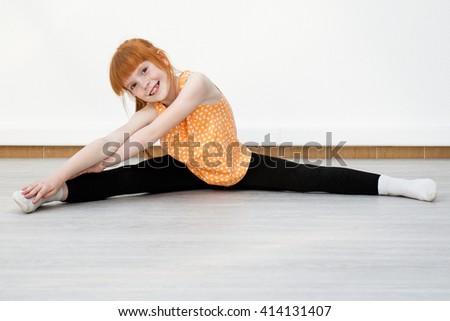 Little girl smiling and doing stretching. The child sits on the floor in the pose of the cross twine.