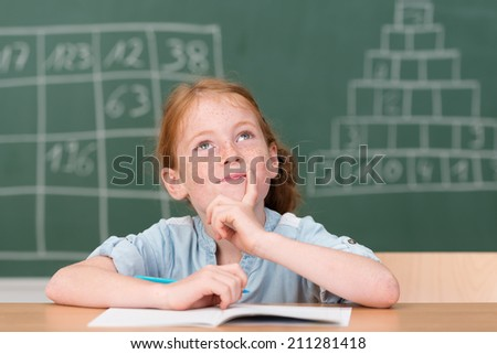 Little girl smiling as she sits at her desk in class writing notes staring up into the air with a pensive expression with the blackboard behind her - stock photo