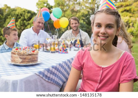Little girl smiling at camera at her birthday party outside at picnic table  - stock photo