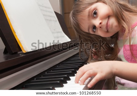 Little girl smiling at piano keyboard - stock photo