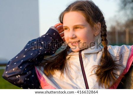 Little girl smiling at the sunset and the green grass backing closeup - stock photo