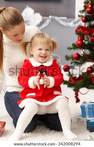 Little girl smiling happy at christmas in mothers' lap.