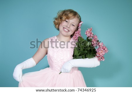 Little girl smiling holding bouquet of pink flowers - stock photo
