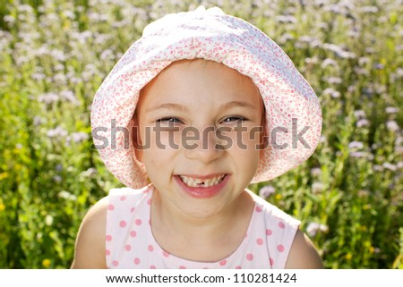 Little girl smiling into the camera lens - stock photo