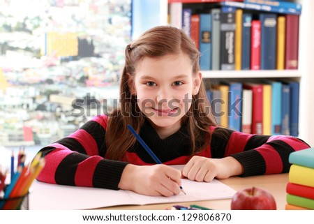 Little girl smiling into the camera while doing her homework - stock photo