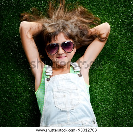 little girl smiling on a green lawn in sun glasses - stock photo