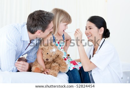 Little girl smiling with her teddy bear against white background