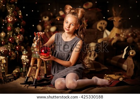 Little girl smiling with long hair bow at the new year interior with wooden horse