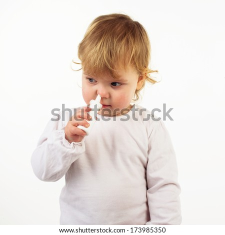 Little girl spraying her nose with nasal spray - stock photo