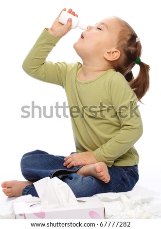 Little girl spraying her nose with nasal spray while sitting on floor, isolated over white - stock photo