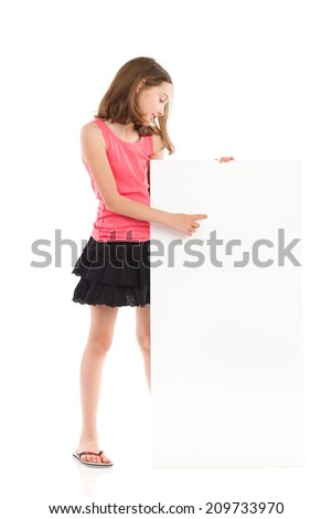 Little girl standing behind blank banner and pointing. Full length studio shot isolated on white. - stock photo