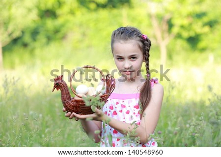 Little girl standing in a green long grass holding a basket in the shape of a rooster with eggs - stock photo