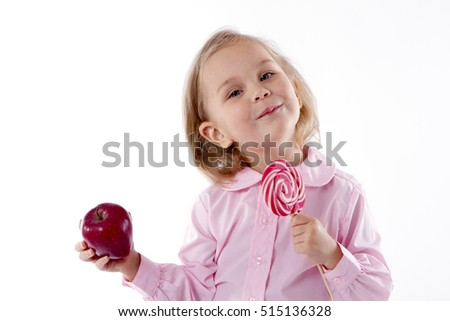 little girl standing in front of a choice to eat an apple or a big lollipop. on a white background