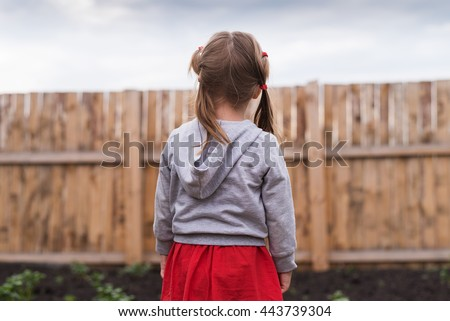 Little girl standing in front of a fence