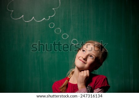 Little girl standing in front of chalkboard with comic cloud drawing on it and she looks pensive but happy - stock photo