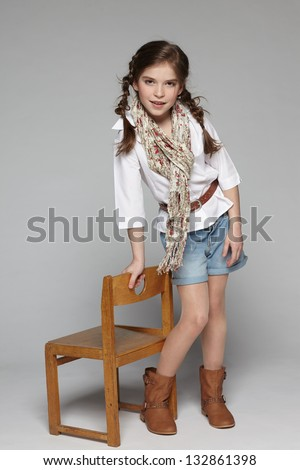 Little girl standing in full length leaning on the wooden chair - stock photo
