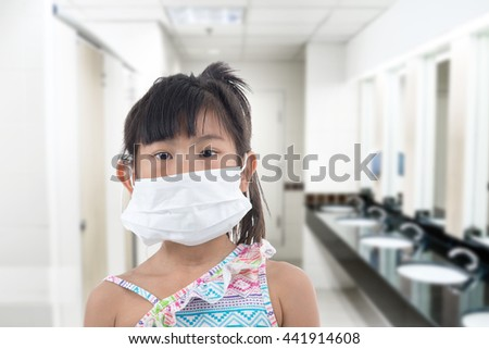 little girl standing in protective mask, white mask, bad smell public toilet - stock photo