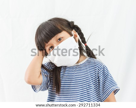 little girl standing in protective mask, white mask, girl standing on white background, - stock photo