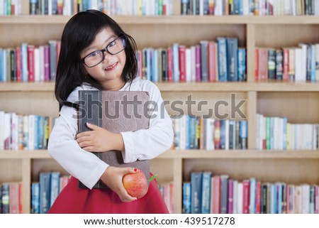 Little girl standing in the library and smiling at the camera while holding a book and apple fruit