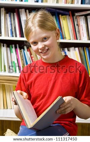 Little girl standing near the bookshelf - stock photo