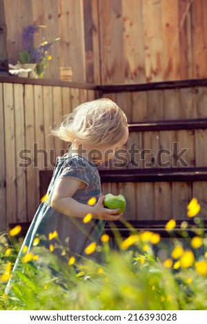 Little girl standing on a country house wooden stairs and holding an apple, natural lighting outdoor shot. Toned photo. - stock photo
