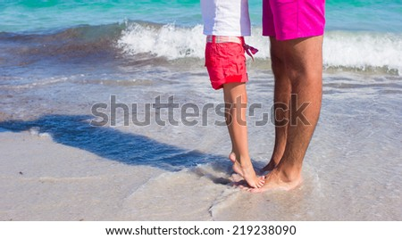 Little girl standing on her father's feet at the white sandy beach