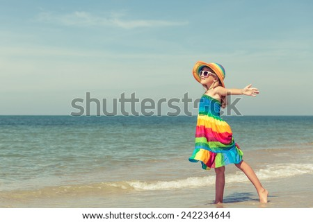 Little girl  standing on the beach at the day time - stock photo