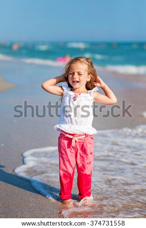 little girl standing on the beach in pink pants and laughting