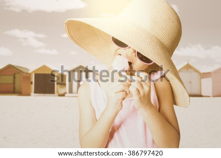 Little girl standing on the beach while wearing a beach hat and sunglasses, enjoying ice cream, shot with an instagram filter - stock photo