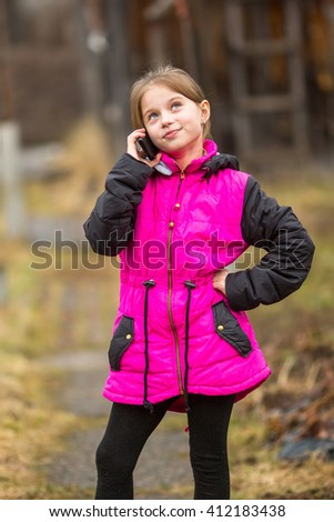 Little girl standing on the street talking on a cell phone. - stock photo