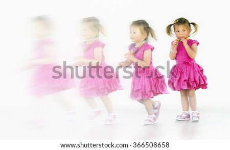 Little girl standing,  running  and blurring in a white background - stock photo