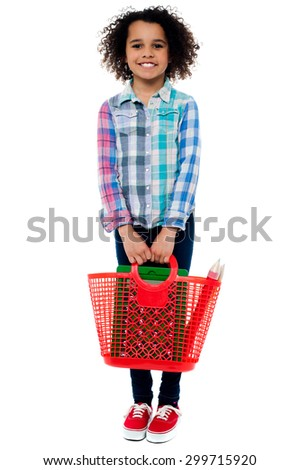 Little girl standing with basket bag over white - stock photo