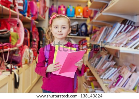 Little girl stands in school department of store with backpack on shoulders, holding several notebooks - stock photo