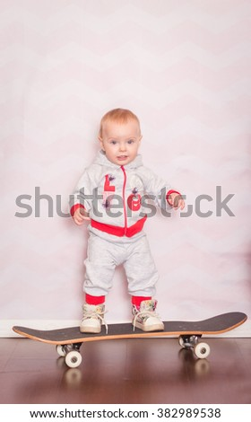little girl stands on a skateboard on a light background - stock photo
