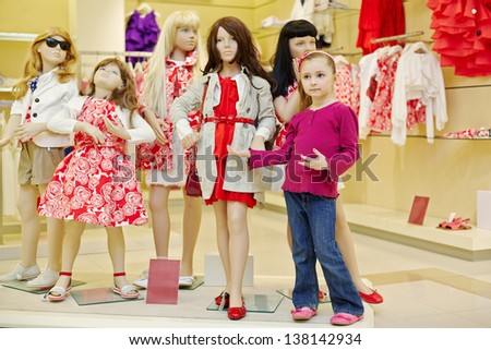 Little girl stands together with group of dressed mannequins and performs one of them - stock photo