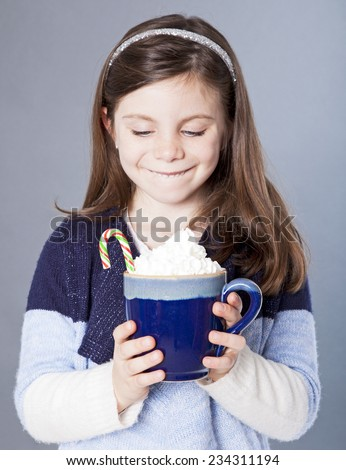 Little girl staring at a delicious cup of hot cocoa with candycane - stock photo