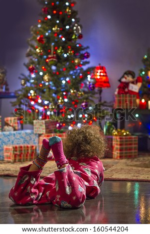 Little girl staring at Christmas tree in pajamas, vertical - stock photo