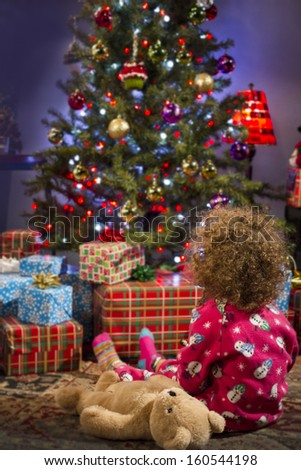 Little girl staring at Christmas tree, vertical
