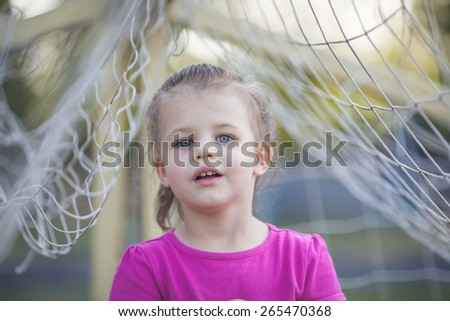 Little girl staying between football net and playing with it