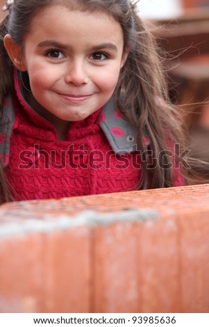 Little girl stood by brick wall