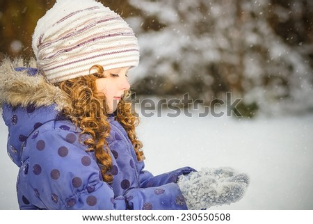 Little girl stretches her hand to catch falling snowflakes. Winter portrait. - stock photo