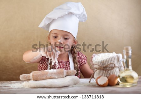Little girl stretching the cookie dough dispersing some flour over it - stock photo