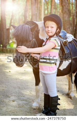 Little girl stroking her pony. Toned image - stock photo