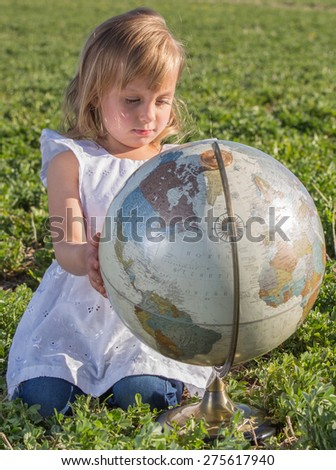 Little girl studying a globe in a hay field. - stock photo