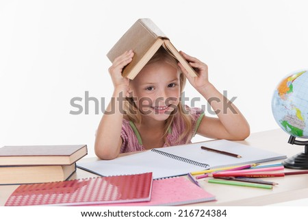 little girl studying literature and smiling. Girl holding book over head while sitting at white table. - stock photo