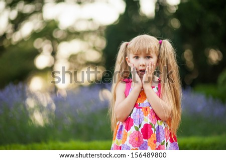Little girl surprised with hands on her face - stock photo
